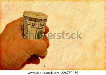 hand holding roll of 100 dollars banknotes, grunge paper background for your message - stock photo