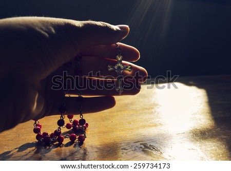 Hand holding rosary towards the light in prayer