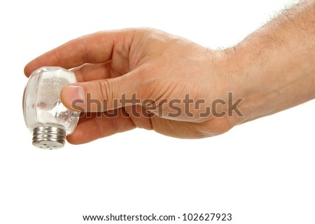 Hand holding salt cellar upside down isolated on white background