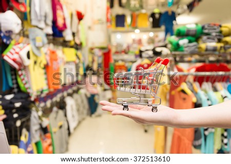 Hand Holding Shopping Cart In The Clothing Store - stock photo
