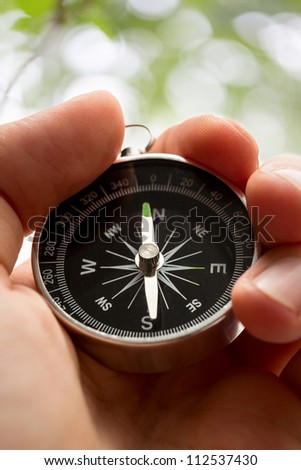 Hand holding silver black compass