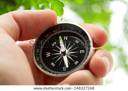Hand holding silver black compass  - stock photo