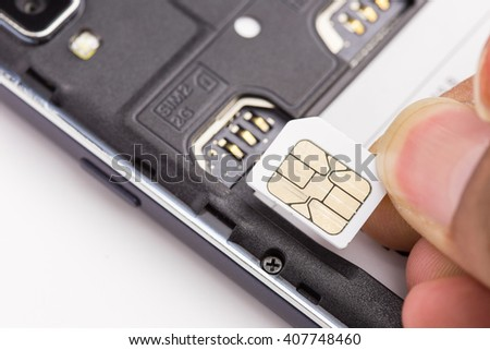 Hand holding sim card before insert to the sim card slot - stock photo