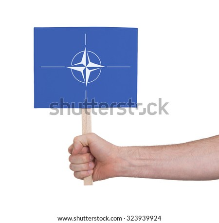 Hand holding small card, isolated on white - Flag of NATO - stock photo