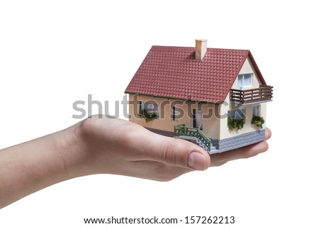 Hand holding small miniature house isolated on white background