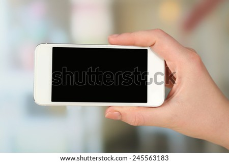 Hand holding smart mobile phone on light blurred background
