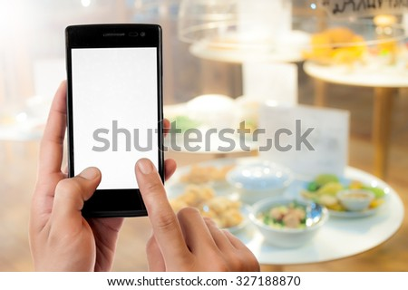 Hand holding smart phone on blurred food background,nuggets and vegetables - stock photo