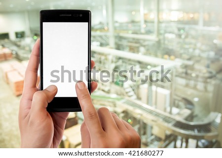 Hand holding smart phone on Manufacturing factory blurred background.