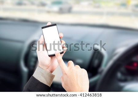 Hand holding smart phone text message in car blur background road safety concept