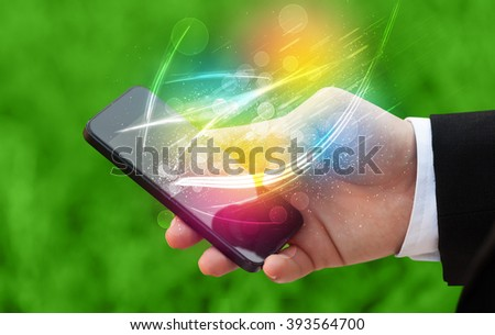 Hand holding smart phone with abstract glowing lines concept - stock photo
