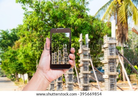 Hand holding smart phone with concrete pillar mold for house construction.