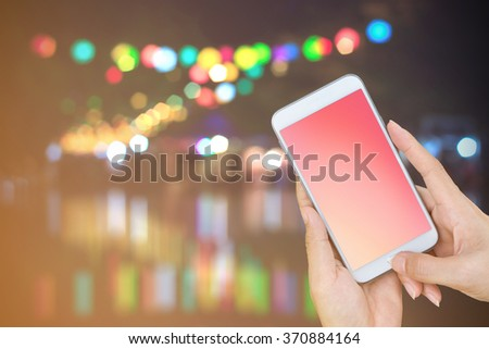 Hand holding smart phone with empty screen on street evening light with abstract bokeh background. - stock photo