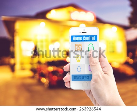 Hand holding smart phone with home control application with blur home background, Smart home concept - stock photo
