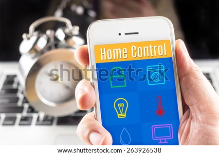 Hand holding smart phone with home control application with clock and computer at background, Smart home concept - stock photo