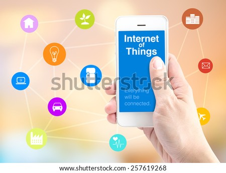 Hand holding smart phone with Internet of things (IoT) word and object icon and blur background, Digital Marketing concept. - stock photo