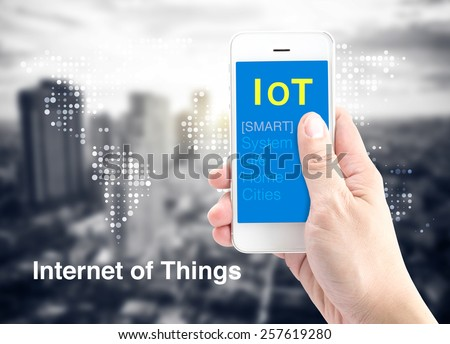 Hand holding smart phone with Internet of things (IoT) word with dot world map and city blur background, Digital Marketing concept. - stock photo