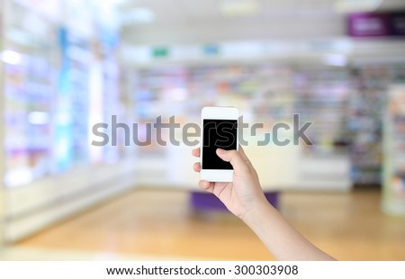 hand holding smart phone with supermarket in blurry for background - stock photo