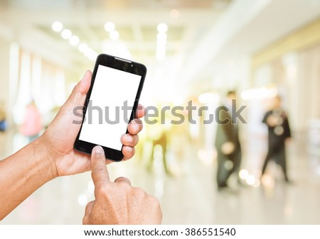 Hand holding smart phone with white screen over blur shopping mall background.  - stock photo