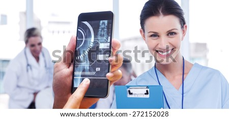 hand holding smartphone against cheerful young surgeon posing with colleagues in background - stock photo