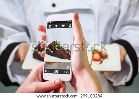 Hand holding smartphone against chef presenting chocolate cake with strawberries - stock photo