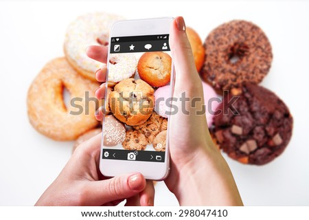 Hand holding smartphone against choice of pastry - stock photo