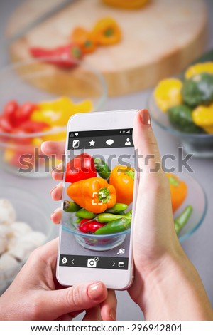Hand holding smartphone against close up of pimentos - stock photo