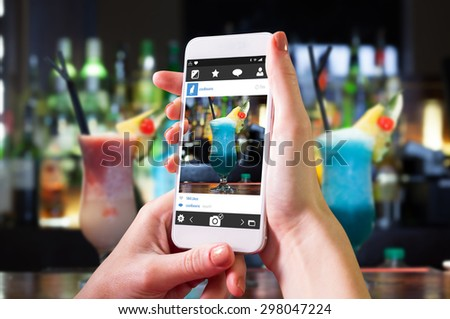 Hand holding smartphone against close up on mouth watering cocktails - stock photo