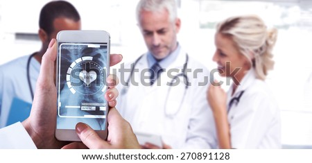 Hand holding smartphone against doctors using a tablet - stock photo