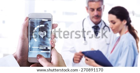 Hand holding smartphone against nurse and doctor looking a file - stock photo