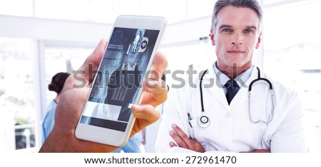 hand holding smartphone against smiling doctor with arms crossed - stock photo