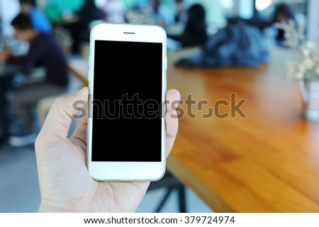 Hand holding smartphone in coffee cafe - stock photo