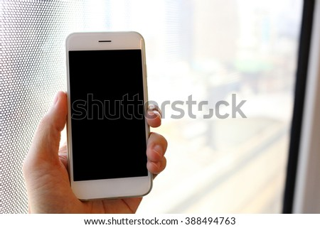 Hand holding smartphone in train