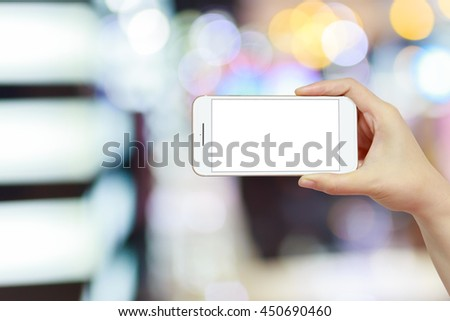 hand holding smartphone isolated white screen on beautiful bokeh light background - stock photo