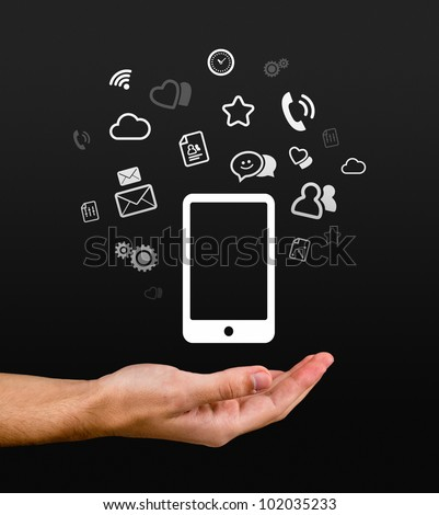Hand holding smartphone, lots of gadgets at your finger tips.