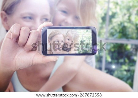 Hand holding smartphone showing against cute little girl and mother on bed - stock photo