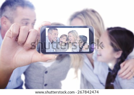 Hand holding smartphone showing against happy family with two children smiling and hugging - stock photo