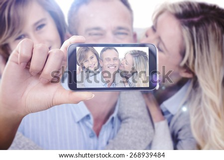 Hand holding smartphone showing against happy father carrying his son and his wife on his back - stock photo