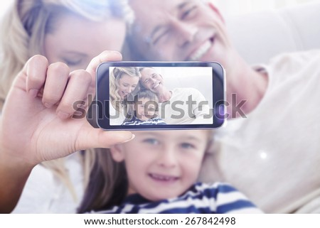 Hand holding smartphone showing against happy parent tickling her cute son on the couch - stock photo