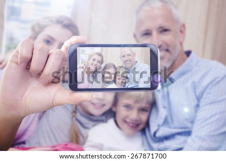Hand holding smartphone showing against happy parents with their children on sofa - stock photo