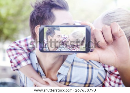 Hand holding smartphone showing against man giving his pretty blonde girlfriend a piggy back - stock photo