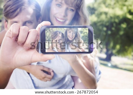 Hand holding smartphone showing against man giving his pretty girlfriend a piggy back in the park smiling at camera - stock photo
