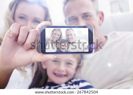 Hand holding smartphone showing against parent cuddling their son on the couch - stock photo