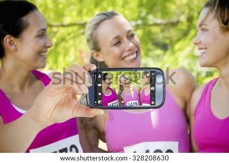 Hand holding smartphone showing against smiling women running for breast cancer awareness - stock photo
