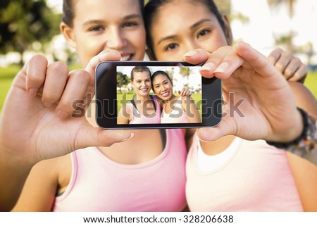 Hand holding smartphone showing against two smiling women wearing pink for breast cancer