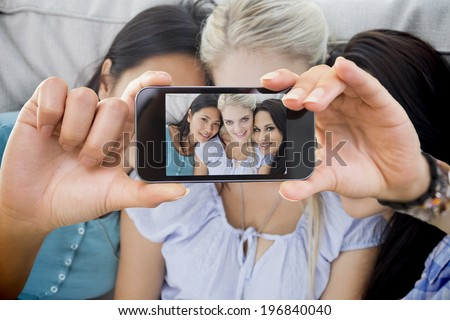 Hand holding smartphone showing close friends smiling at camera - stock photo