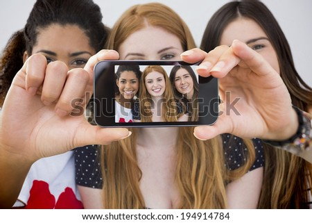 Hand holding smartphone showing close up portrait of cheerful female friends - stock photo