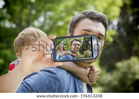 Hand holding smartphone showing father carrying young boy on back at park - stock photo