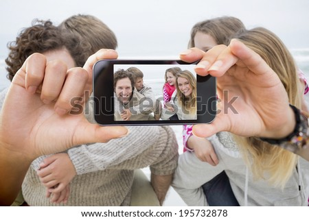 Hand holding smartphone showing happy couple piggybacking kids at beach - stock photo