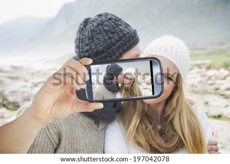 Hand holding smartphone showing man kissing a woman on rocky landscape - stock photo