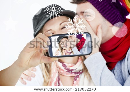 Hand holding smartphone showing photo against hanging decorations - stock photo